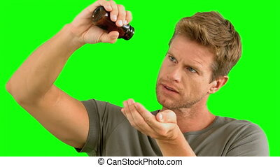 Man pouring out pills on green screen in slow motion