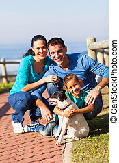 family at the beach with pet dog