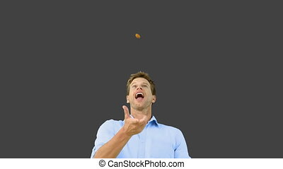 Man catching an orange segment with mouth on grey screen in...