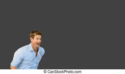 Smiling man jumping on grey screen