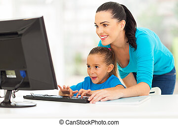 happy mother teaching daughter computer