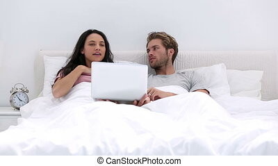 Couple using the laptop together at home in bed