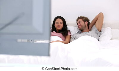 Couple watching tv together at home in bed