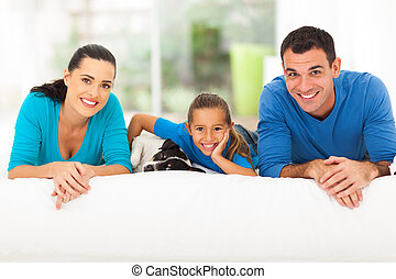 happy family lying on bed with pet dog