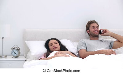 Man talking on phone while his partner is sleeping in bed at...