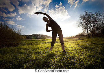 woman stretching out on the field doing yoga before jogging...