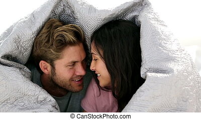 Couple chatting under the covers at home in bed