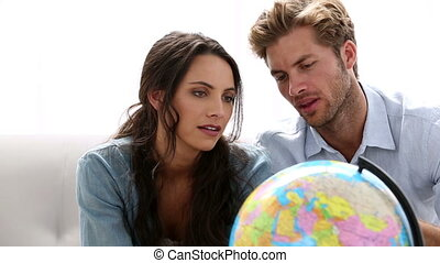 Couple looking at globe and picking