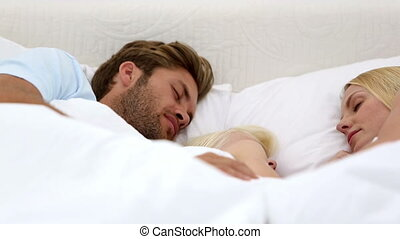 Parents and daughter sleeping together at home in bed