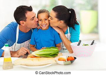 loving parents kissing little daughter in kitchen