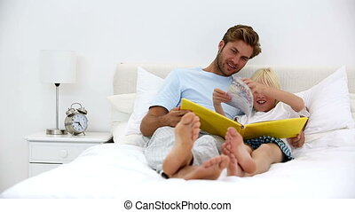 Father and son reading book together at home in bed