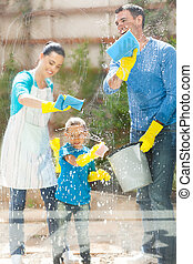 happy family cleaning home window