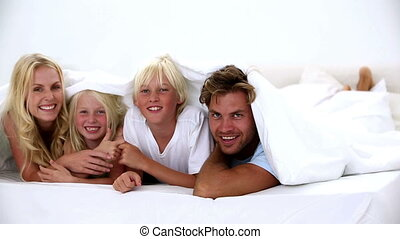 Happy family under the covers playing and smiling at camera