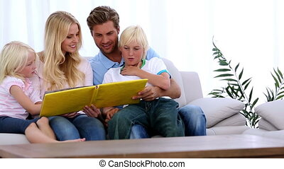 Family reading storybook together at home on the couch