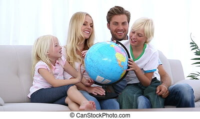 Family looking at globe together at home on the couch