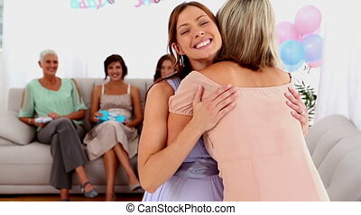 Pregnant woman receiving hugging her friend and getting a...
