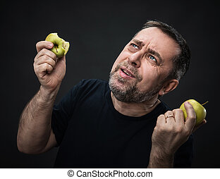 Middle-aged man with a green apples