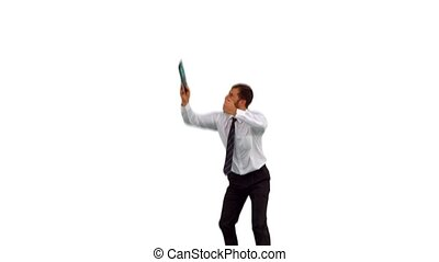 Businessman jumping up holding tablet pc in slow motion