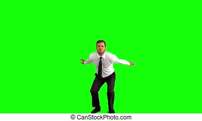 Businessman jumping and punching the air on green screen in...