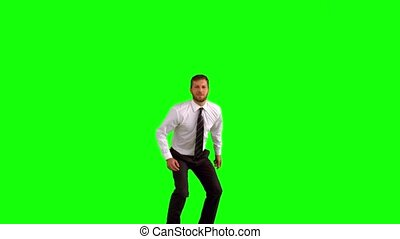 Businessman jumping up for joy on green screen in slow...