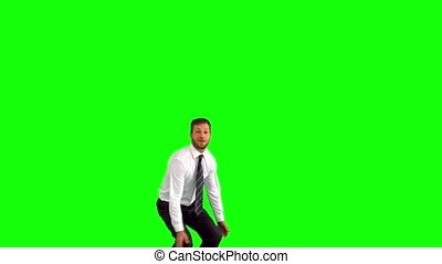 Businessman jumping and giving thumbs up on green screen in...