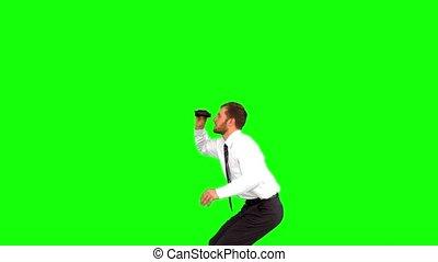 Businessman looking through binoculars while jumping on...