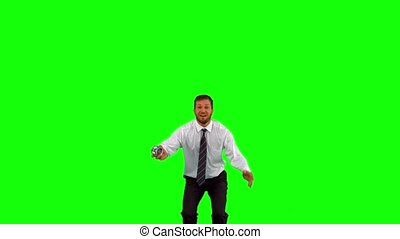 Businessman holding alarm clock jumping on green screen in...
