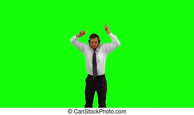 Businessman listening to music while jumping up and cheering...