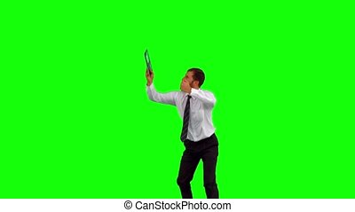 Businessman holding tablet pc jumping up on green screen in...