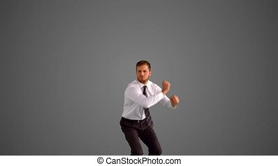 Businessman jumping and stretching on grey background n slow...
