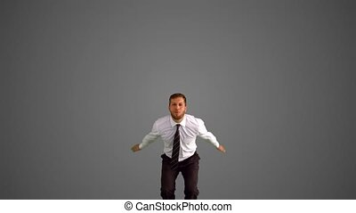 Businessman jumping and doing the splits on grey background...