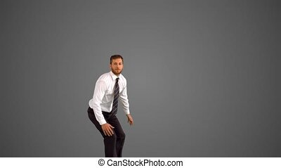 Businessman leaping up and grabbing legs on grey background...