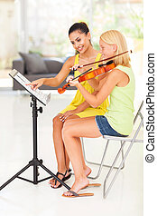 music teacher pointing notes for violin student
