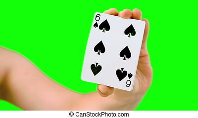 Hand shuffling and pushing cards towards camera on green...