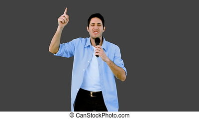 Man singing into microphone on grey
