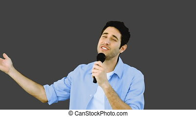 Man singing into microphone with emotion on grey background...