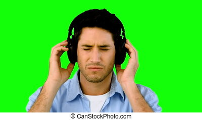 Man listening to music with headphones on green screen in...