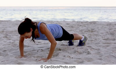 Woman exercising on the beach doing push ups