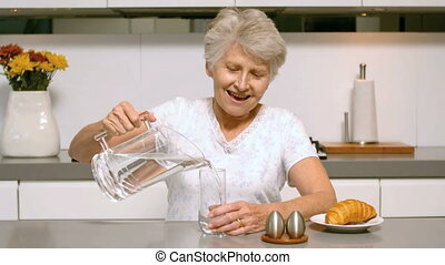 Happy woman pouring a glass of wate