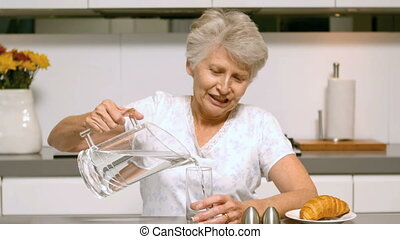 Retired woman pouring a glass of water for breakfast in the...