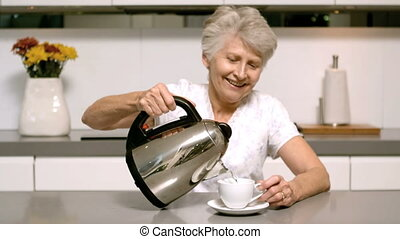Elderly woman pouring boiling water from kettle into cup in...