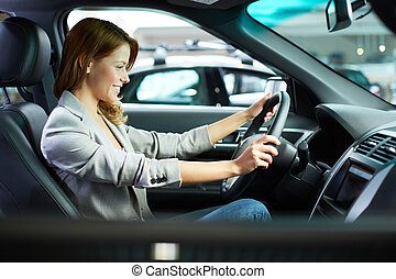 Female in new car - Photo of young woman choosing a new car...