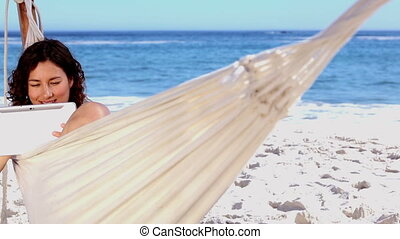 Smiling woman using tablet in a hammock on a sunny beach