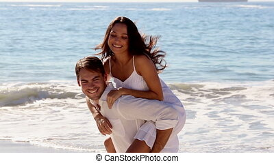 Man giving a piggy back to his girlfriend on a sunny beach