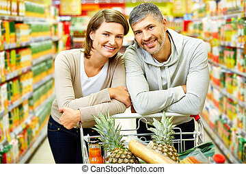Couple of consumers - Image of happy couple with cart...