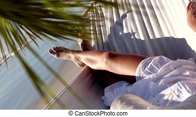 Woman relaxing in a hammock under a