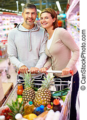 Happy customers - Image of happy couple with cart choosing...