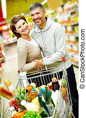 Couple in supermarket - Image of happy couple with cart full...