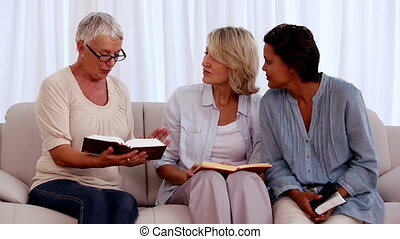 Retired friends studying the bible together at home on the...
