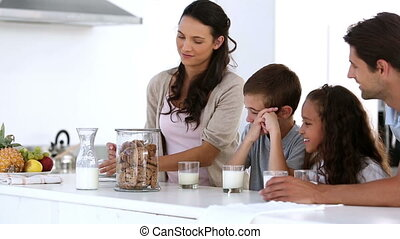 Mother offering cookies to her family at home in kitchen